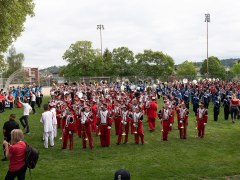 Multiple marching bands crammed onto a local playfield practicing before the parade